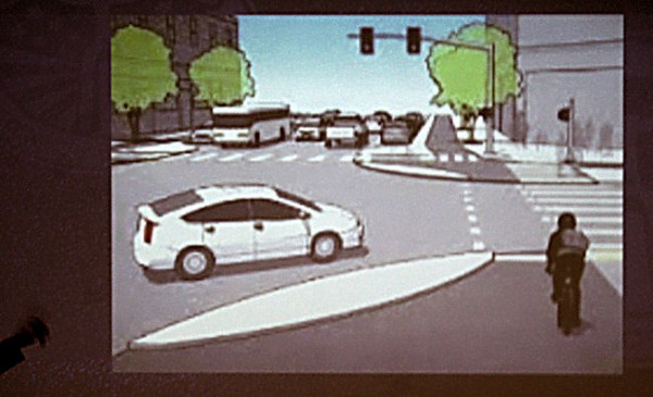 Pete Stidman shows a plan for right-turning traffic to yield to through-traveling bicyclists.
