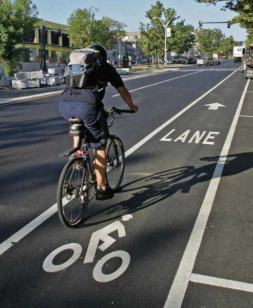 """Bike lanes designate an exclusive space for bicyclists through pavement markings and signs, and are located adjacent to motor vehicle traffic."" Photo by George Rizer for the Boston Globe"